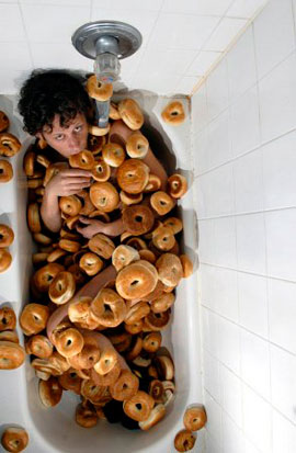 Jamie Kastner in a bathtub filled with bagels
